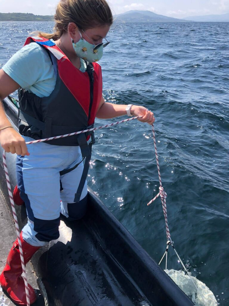 Image shows Maria Mcguinness lowering a plankton net into the water. She is holding the rope. She is wearing a pale blue t shirt, green facemask, red buoyancy aid, blue salopettes and red wellington boots