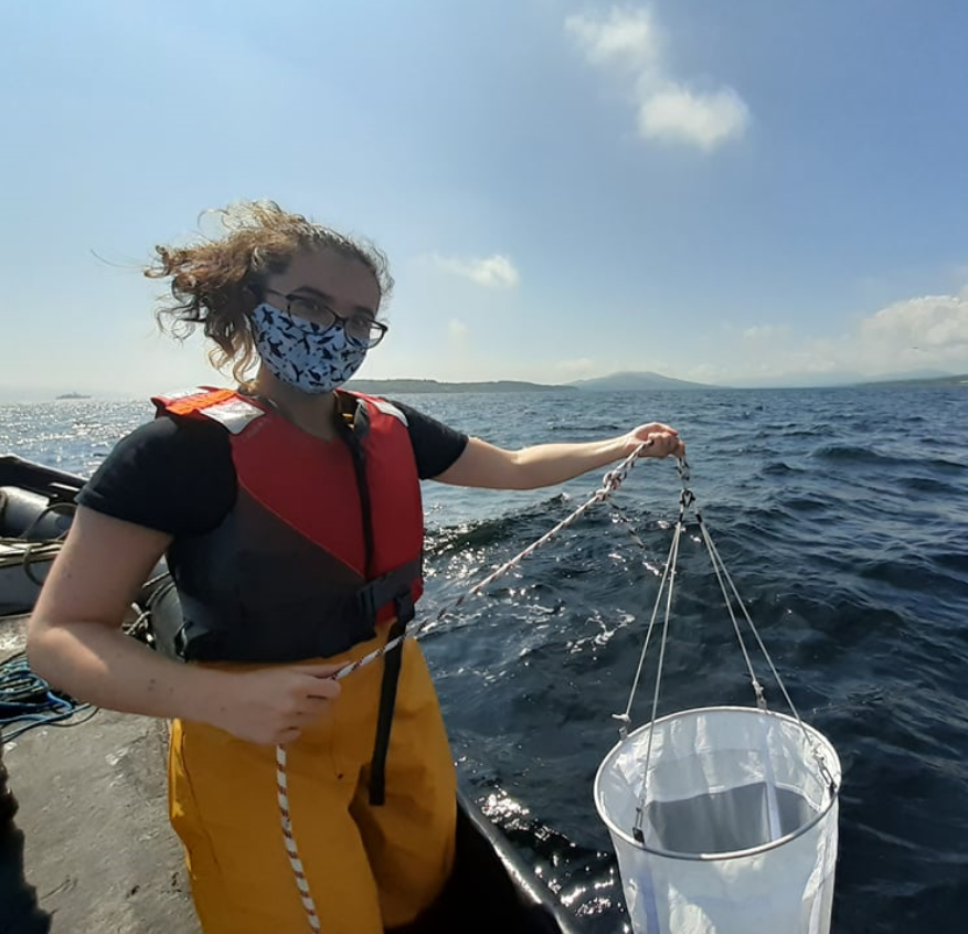 Pictured is Hannah Brownlow. She is wearing fishermans overalls, a red buoyancy aid, a black t-shirt and blue face mask with penguins on it. She is out on a boat in the sun and is holding a plankton net just above the waters surface.