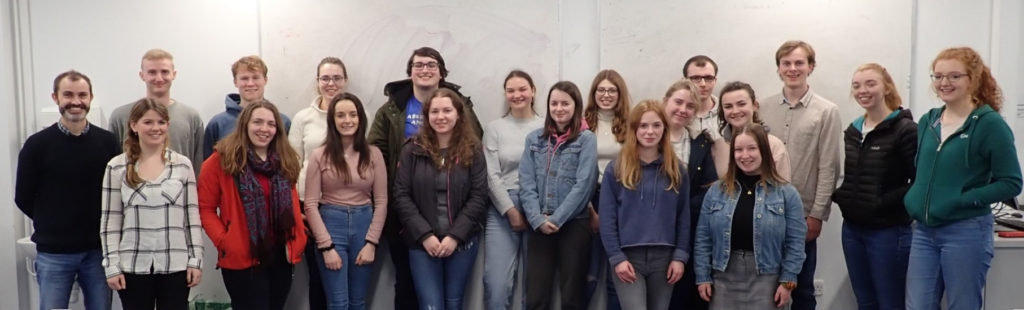 The image shows Tom Doyle, Maria McGuinness and 18 students in one of the teaching labs in UCC.
