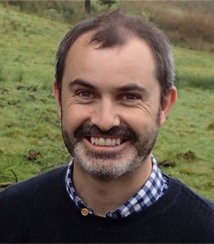 Image shows team lead, Tom Doyle. He has dark short hair and a beard and is in front of a grassy background. He is smiling at the camera