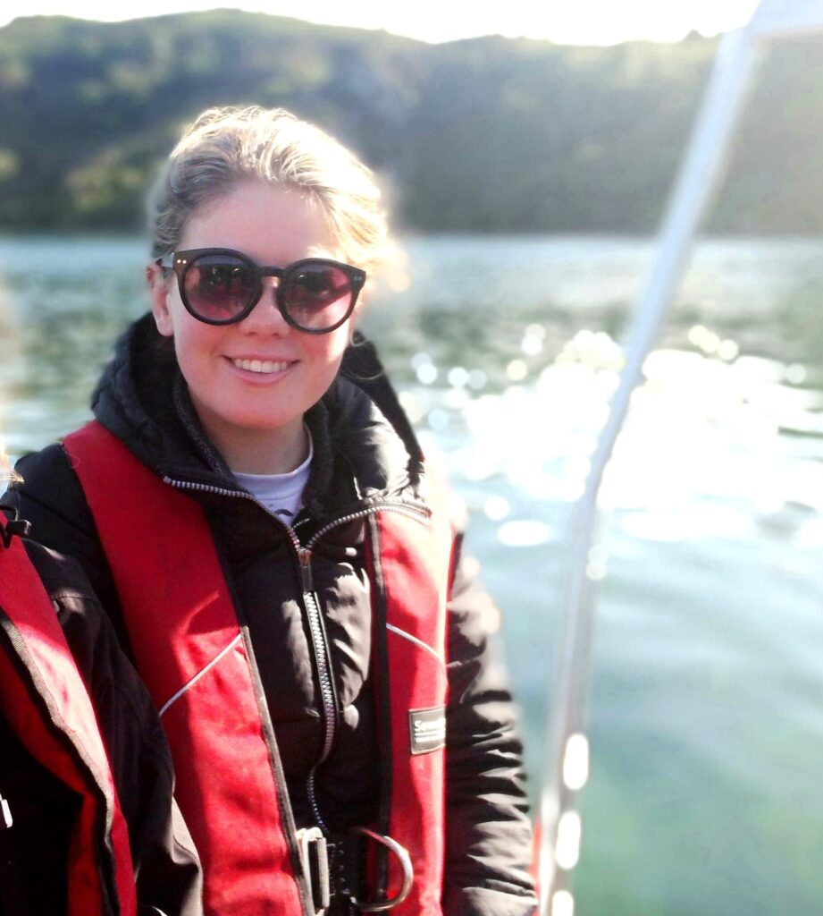 Maria McGuinness is pictured here. She is on a boat in a black jacket wearing a red life jacket. She has blonde hair tied back and is wearing sunglasses. Water is visible in the background