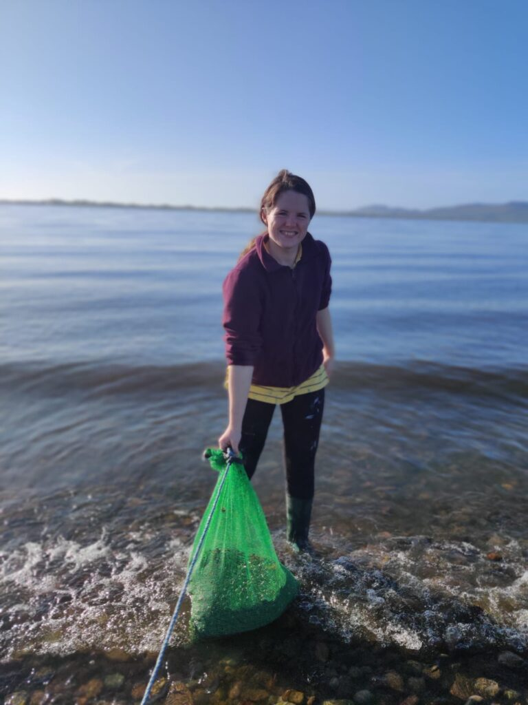 The image shows Grainne Cronin-O'Reilly. She is wearing a purple jumper, black trousers and dark green wellies. She is pictured holding a green mesh bag full of oysters and is on a beach. She is standing in the water.