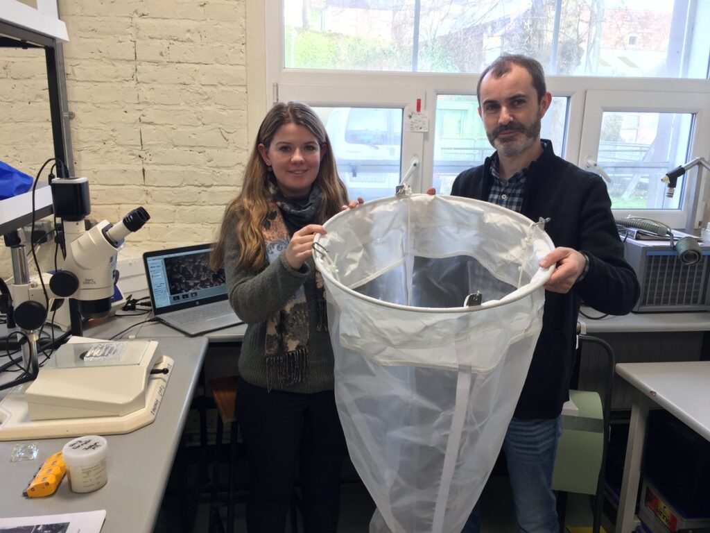 Team lead, Tom Doyle, and PhD student Maria McGuinness, holding a plankton net in the plankton lab. A stereoscope and laptop are visible in the background.
