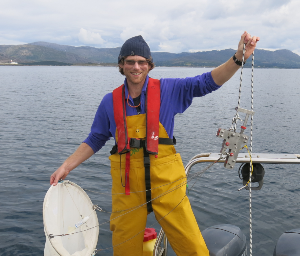 Image shows Damien Haberlin out on a boat. He is wearing fishermans overalls, a hat, sunglasses and is holding a plankton net in one hand and the rope in the other