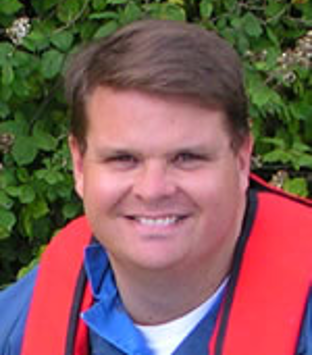 Image shows close up of Professor Rob McAllen. He is smiling at the camera. He is wearing a blue shirt and red lifejacket. He has short brown hair.